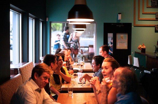 přátelé sedící v restauraci u několika stolů
